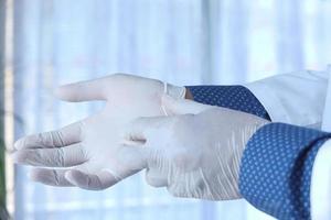 man sätter på vita medicinska handskar foto