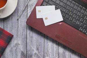 kreditkort på en bärbar dator på träbakgrund
