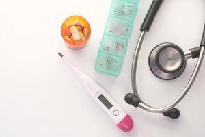 piller, termometer och stetoskop på vit bakgrund