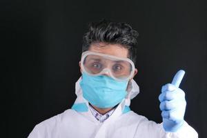 läkare i ppe håller tummen upp