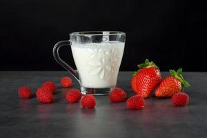 jordgubbar och ett glas mjölk på en svart bakgrund