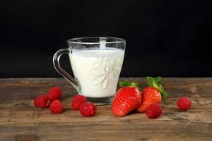 jordgubbar och en mjölkdryck på ett träbord