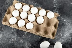råa kycklingägg i en ägglåda på marmorbakgrund foto