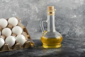 råa kycklingägg i en ägglåda med en glasflaska olja foto