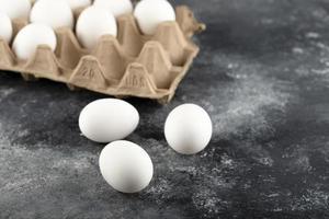 tre råa kyckling färska ägg på en marmor bakgrund foto
