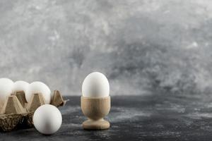 rå kycklingägg i en äggkopp med en ägglåda på marmorbakgrund foto