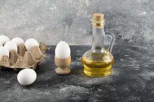 rå kycklingägg i en äggkopp med en ägglåda och ett glas olja på marmorbakgrund foto
