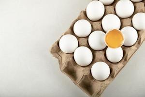råa kycklingägg i en ägglåda på en vit bakgrund foto