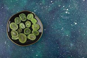 torkade skivor av kiwi på en svart platta foto
