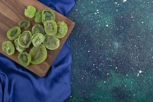 torkade skivor av kiwi på en träskiva foto
