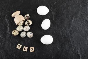 vaktel och kycklingägg på en svart bakgrund foto