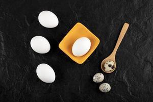 vaktelägg och kycklingägg på svart bakgrund foto