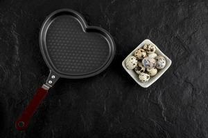 skål med vaktelägg runt en tom hjärtformad kastrull