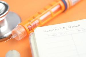 insulinpenna och veckoplanerare på bordet