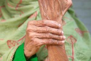 äldre asiatisk kvinna som lider av smärta i handleden foto