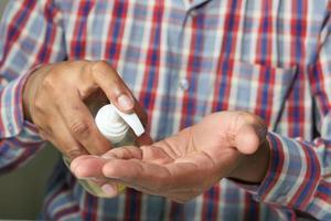 närbild på personen som använder handdesinfektionsmedel