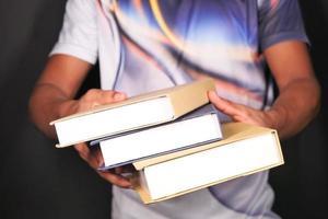 person som rymmer tre stora böcker på svart bakgrund
