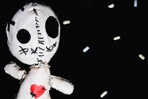 voodoo docka på svart bakgrund foto