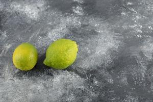 två gröna färska citroner på en marmorbakgrund foto