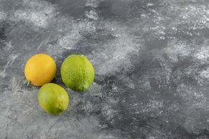 gula och gröna citroner på en marmorbakgrund foto