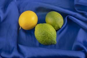 gula och gröna citroner på en blå duk foto