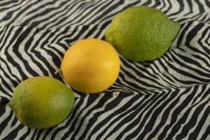 gula och gröna citroner på en duk foto