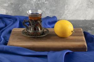 ett glas te med en citron på en träskärbräda foto