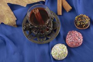 färgglada söta munkar med en kopp te foto