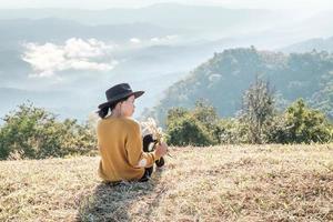 kvinna som håller ris medan du sitter på ett berg foto