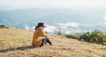 kvinna som kopplar av på ett berg foto