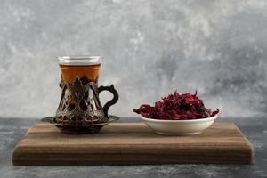 en glas kopp varmt te med torkade blommor på en träskärbräda foto