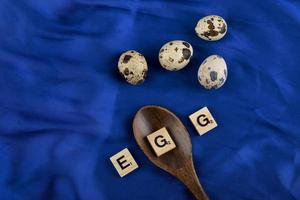 vaktelägg med en träsked och träbokstäver som stavar ordet ägg på en blå satinduk foto