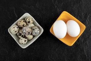 tre vaktelägg och kycklingägg på en svart bakgrund foto