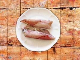 bläckfisk på vit platta på träbord bakgrund foto