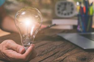 en person som håller en glödlampa bredvid en bärbar dator, nya idéer koncept foto