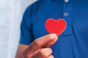 man som håller rött hjärta foto