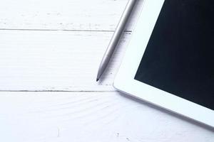 digital tablet och penna på neutral bakgrund