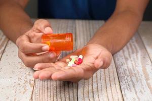 närbild av manhand som tar medicin
