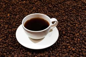 vitt kaffemugg på kaffebönabakgrunden foto