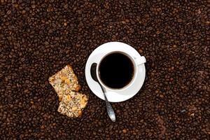 vitt kaffemugg och kakor på bakgrunden för kaffebönor foto