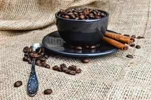 svart kaffemugg full av organiska kaffebönor och kanelstänger på linneduk foto