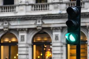 gröna trafikljus för bilar på en suddig byggnad bakgrund foto
