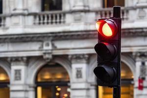 röda trafikljus för bilar på en suddig byggnad bakgrund foto