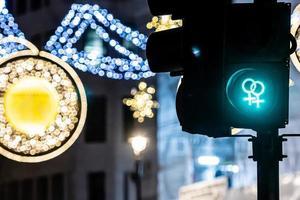 fotgängarsemafor med grönt ljus och defokuserad juldekorationer foto