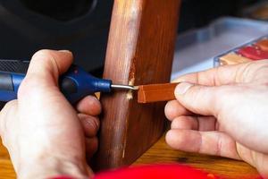 person som reparerar trä foto