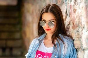utomhus porträtt av vacker, ung kvinna i solglasögon foto