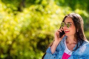 vacker, emotionell, ung kvinna i solglasögon som pratar i telefon foto