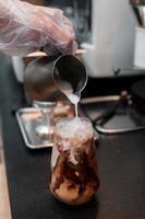 barista hälla mjölk i ett glas iskaffe foto