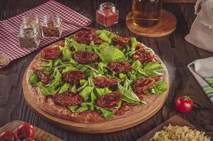 brasiliansk pizza med tomatsås, mozzarella, rucola, torkad, tomater och oregano foto