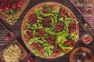 brasiliansk pizza med tomatsås, mozzarella, rucola, torkade tomater och oregano foto